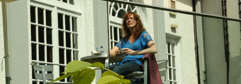 Image of a lady sitting on a terrace outside a hotel